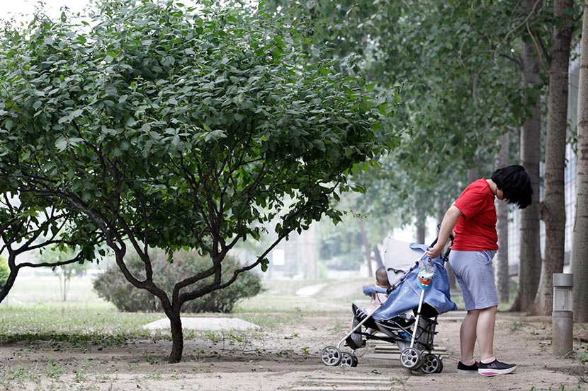 Sisi takes her baby girl through the park in a stroller in Beijing, June 7, 2016. Han Meng/Sixth Tone
