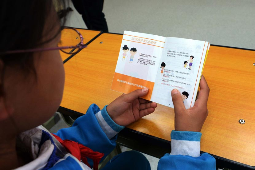 A female student reads a booklet about student safety at an elementary school in Beijing, Oct. 20, 2014. IC
