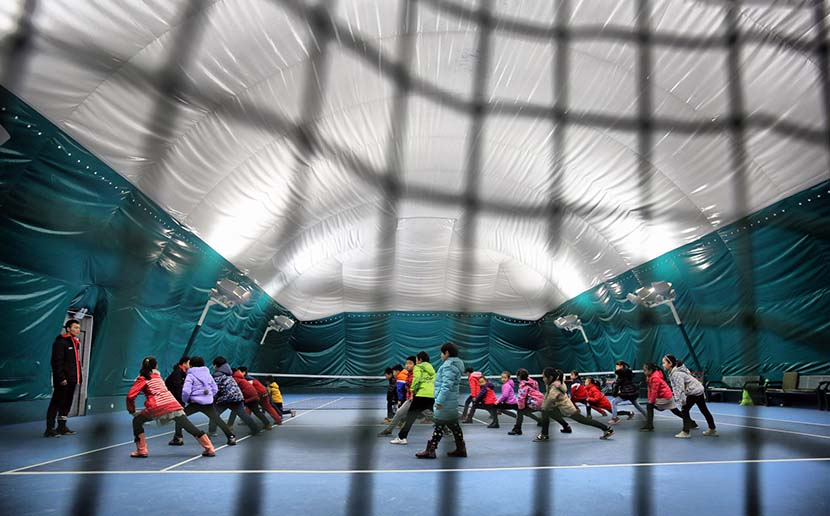 Students at Huaxing Primary School attend gym class in an indoor stadium to avoid the smog in Shijiazhuang, Hebei province, Dec. 9, 2016. The primary school built the stadium with a ceiling that can filter out small pollution particles. IC