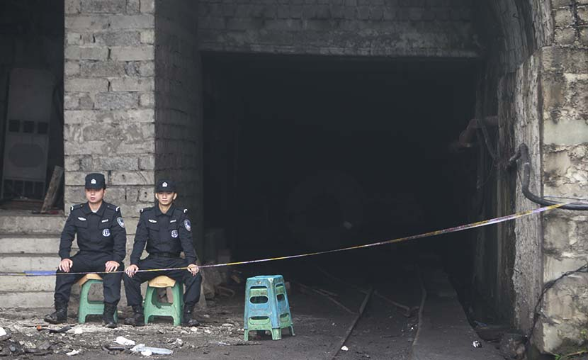 Two security guards sit at the entrance to the Jinshangou coal mine, where a gas explosion killed 33 people in Chongqing, Nov. 2, 2016. Feng/VCG