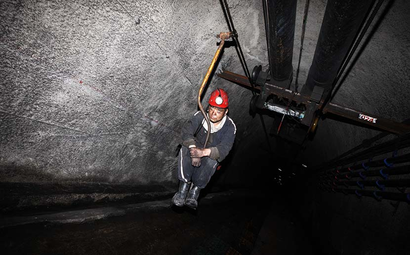 A worker descends into a coal mine using a simple elevator device in Suzhou, Anhui province, June 16, 2016. Hoo Mei/VCG