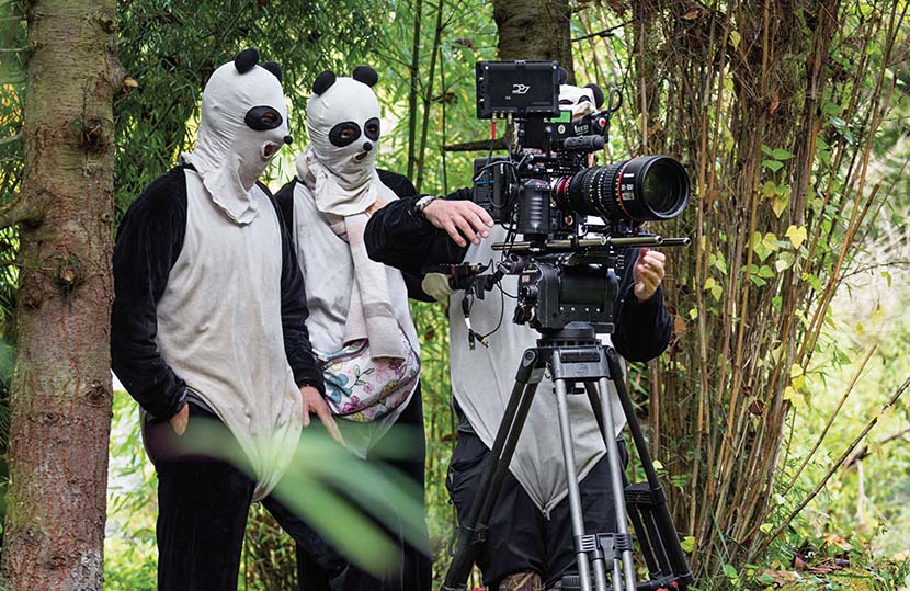 Staff from the crew of 'Born in China,' dressed in panda costumes, film a baby panda in Sichuan province.