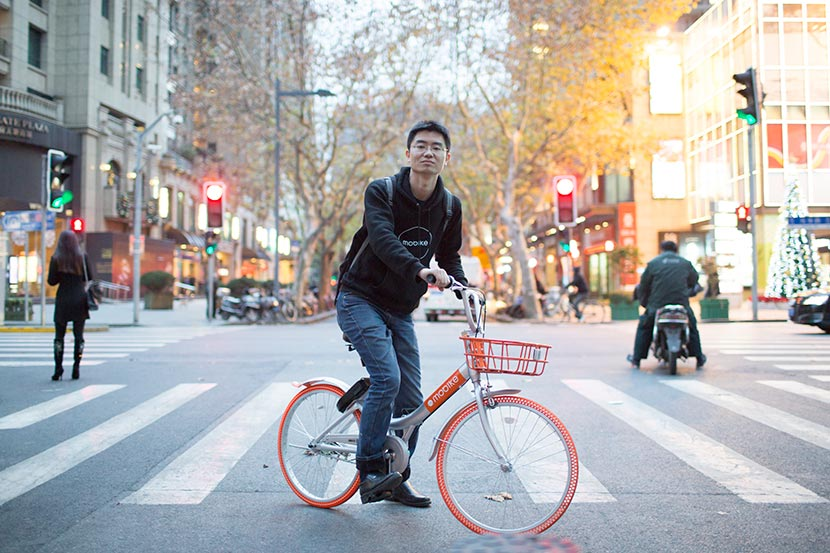 Michael Yao, Mobike general manager for Shanghai, poses for a photo on a Mobike shared bicycle, Shanghai, Dec. 14, 2016. Zhou Pinglang/Sixth Tone
