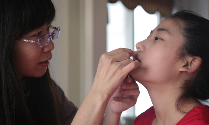 Du Haihong cleans her daughter's nostrils with a cotton swab doused in saline at home in Baoding, Hebei province, Dec. 23, 2016. Wu Yue/Sixth Tone