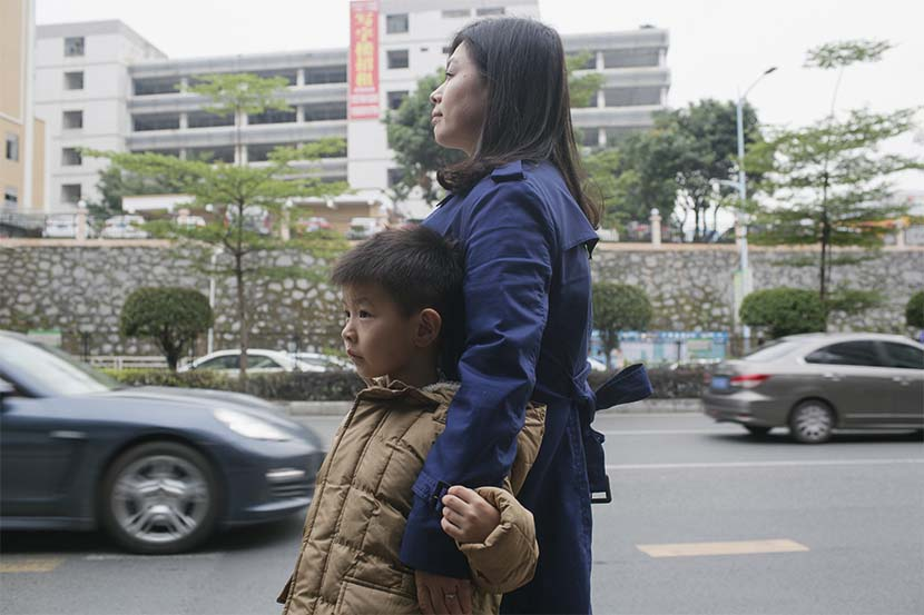 Lan Yanfei waits for a bus with her son in Shenzhen, Guangdong province, Dec. 24, 2016. Zhou Pinglang/Sixth Tone