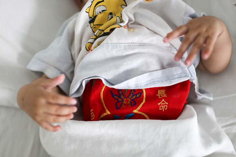 An abandoned infant girl lies on a hospital bed in Jinan, Shandong province, June 14, 2014. The cloth wrapped around her stomach reads 'live a long life.' Quan Yi/Sixth Tone