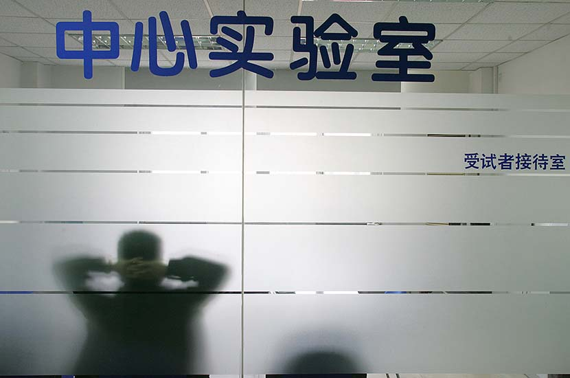 A man sits in a testing room for subjects, waiting for the results of CD4 cell testing, at a hospital in Shanghai, Dec. 6, 2006. Xu Haifeng/Sixth Tone