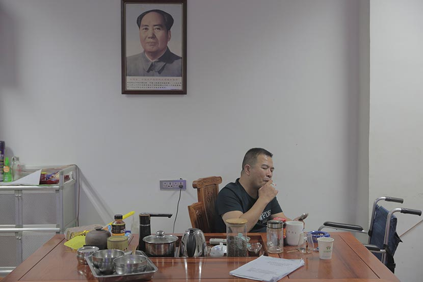 Wang Jianghe smokes in his office underneath a portrait of Mao Zedong, Paizhouwan Township, Hubei province, Aug. 6, 2016. Zhou Pinglang/Sixth Tone