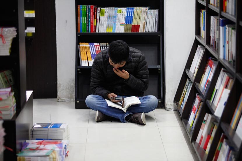 A man looks at his cellphone in a book store in Xianyang, Shaanxi province, Nov. 12, 2014. Tian Ye/IC