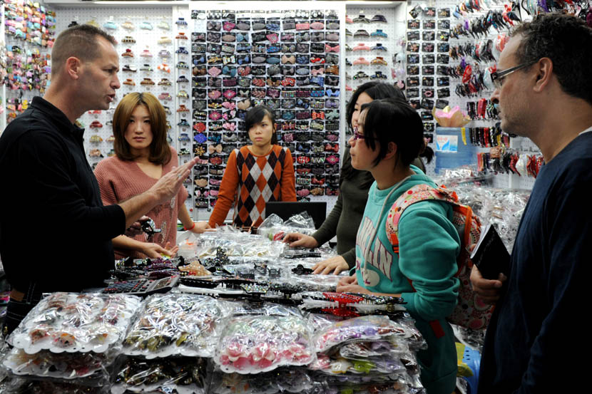 A foreigner negotiates a price with Chinese shop owners at Yiwu International Trade City, Zhejiang province, Nov. 24, 2011. Zhang Jiancheng/VCG