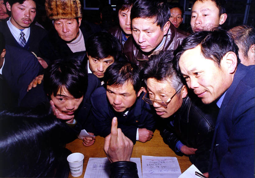 A group of farmers listen to an Yiwu entrepreneur giving business advice in Longyou, Zhejiang province, Feb. 8, 2001. Fu Yongjun/VCG