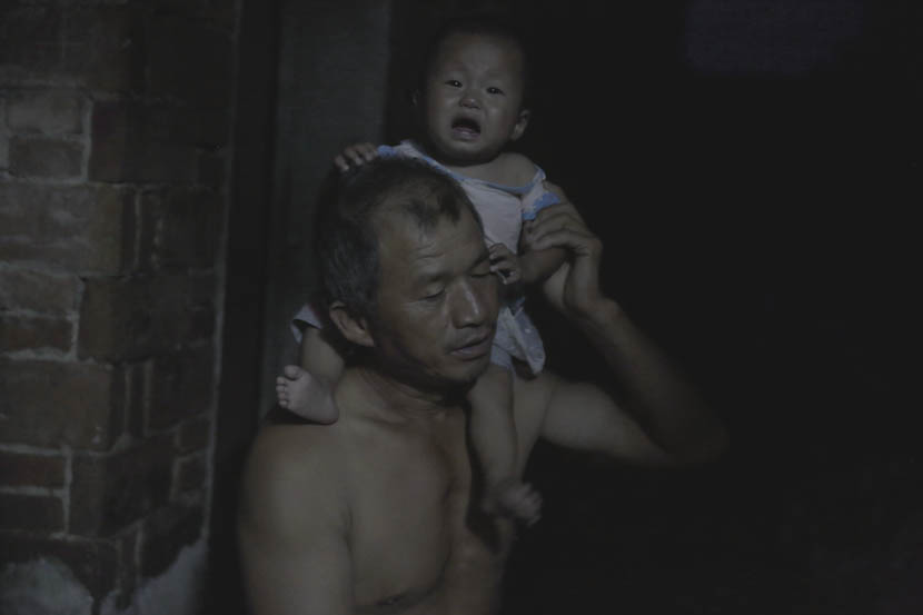 Jin Chengyue holds his baby grandson on his shoulder at home in Paizhouwan Township, Hubei province, Aug. 7, 2016. Zhou Pinglang/Sixth Tone