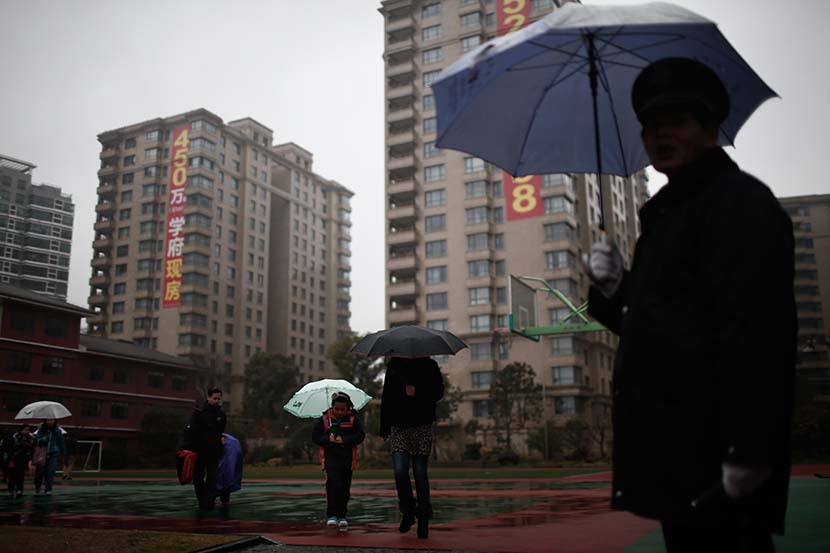 Parents pick up their kids from school as advertisements for 'xuequfang,' or school district apartments, hang on the high-rise buildings in the background, Shanghai, Feb. 17, 2014. Yang Yi/Sixth Tone