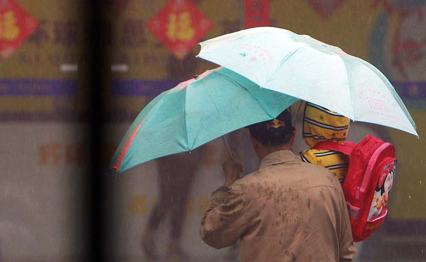 A father takes his son to an English training center in the rain in Nanjing, Jiangsu province, March 29, 2014. VCG