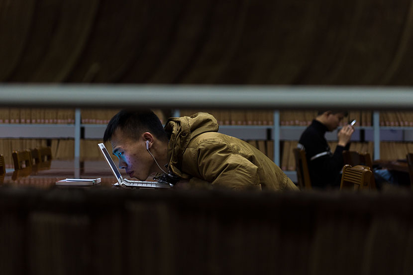 A visually impaired student studies for the national college entrance exam at a library in Changchun, Jilin province, Nov. 17, 2015. VCG
