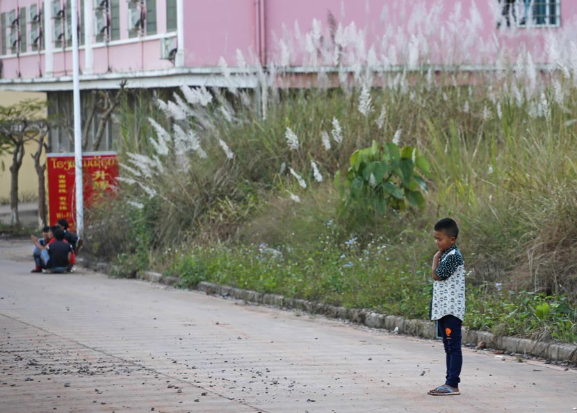 Wang Chao's younger brother stands in the street, while migrant workers gather nearby in Boten, Laos, Nov. 19, 2016. Jia Yanan/Sixth Tone