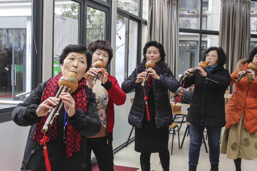 Several older women practice playing the hulusi, a Chinese wind instrument, at Shanghai University for the Elderly, Dec. 27, 2016. Cai Yiwen/Sixth Tone