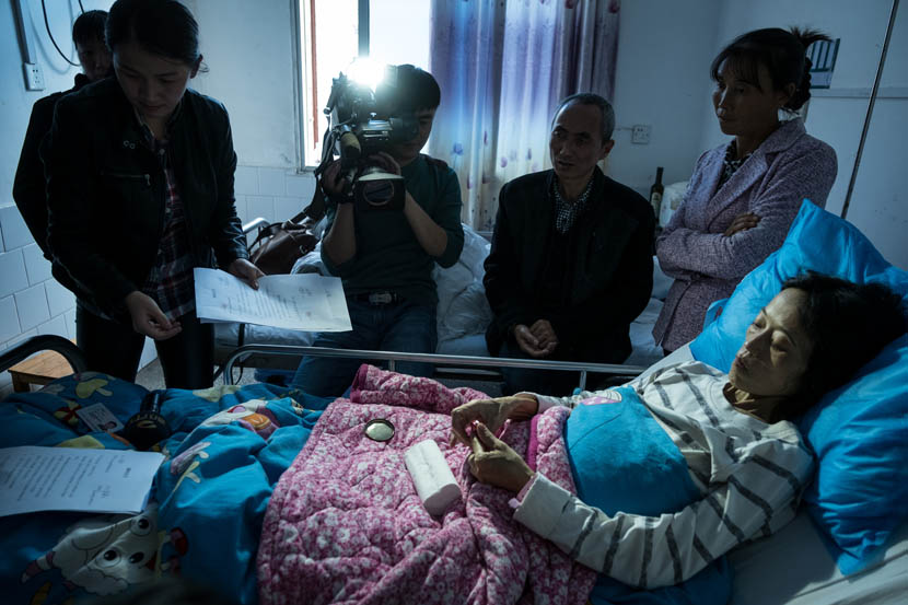Liu Fulan is filmed signing the adoption agreement at Chaling County People's Hospital, Hunan province, Nov. 4, 2016. Zhou Na/Sixth Tone