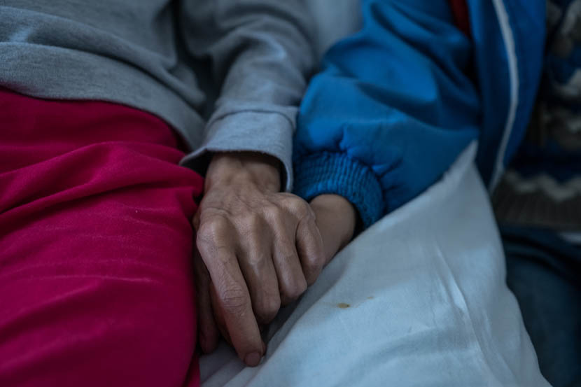 Liu Fulan holds her son's hand as she lies in bed at Chaling County People's Hospital, Hunan province, Nov. 6, 2016. Zhou Na/Sixth Tone
