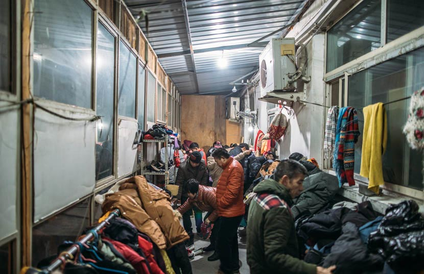 Migrant workers shop at a secondhand store in Pi Village, Beijing, Jan. 15, 2017. Zou Biyu/IC
