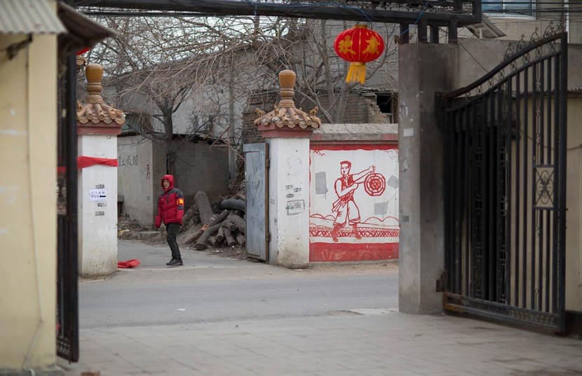 A man with a red armband patrols in Pi Village, Beijing, Jan. 15, 2017. Yang Jia/IC