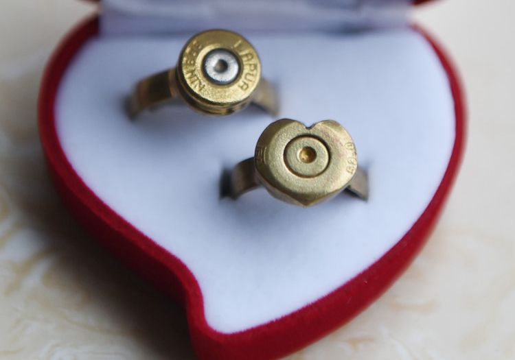 Two wedding rings crafted from bullets sit in a display box, Tonghua, Jilin province, Aug. 30, 2016. VCG