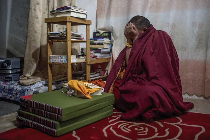 Drukyab, a Buddhist monk, environmental activist, photographer, and filmmaker, chants in his room at a monastery on the Tibetan Plateau, March 20, 2016. He has been independently documenting the Tibetan Plateau's endangered flora and fauna since 2007. Luc Forsyth for Sixth Tone