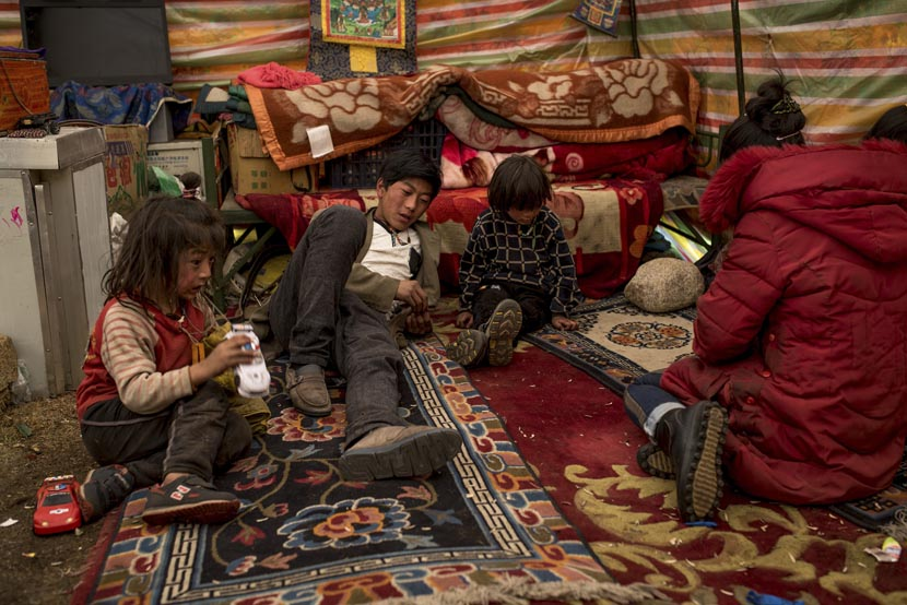 Members of the nomadic Sori family sit inside their living room tent at their winter camp in the Amdo region of the Tibetan Plateau, March 20, 2016. Luc Forsyth for Sixth Tone