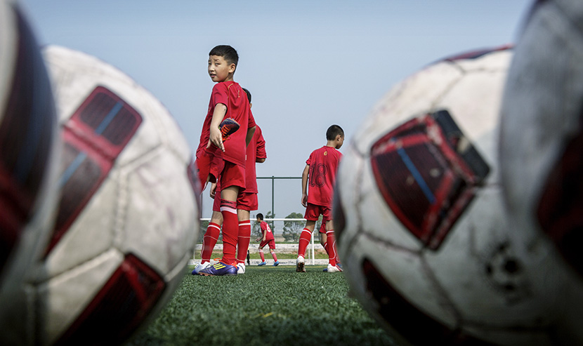 A young boy stretches while waiting his turn to play during a training session at the Evergrande International Football School near Qingyuan, Guangdong province, June 14, 2014. Kevin Frayer/Getty Images/VCG