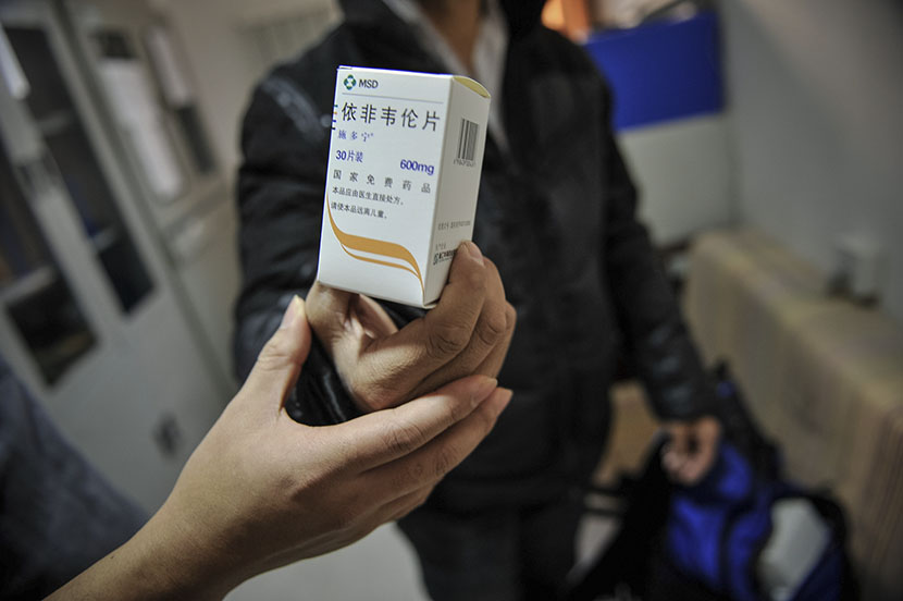 A person holds a package of free antiretroviral medication provided by the Chinese government, Tianjin, Nov. 23, 2016. You Sixing/VCG