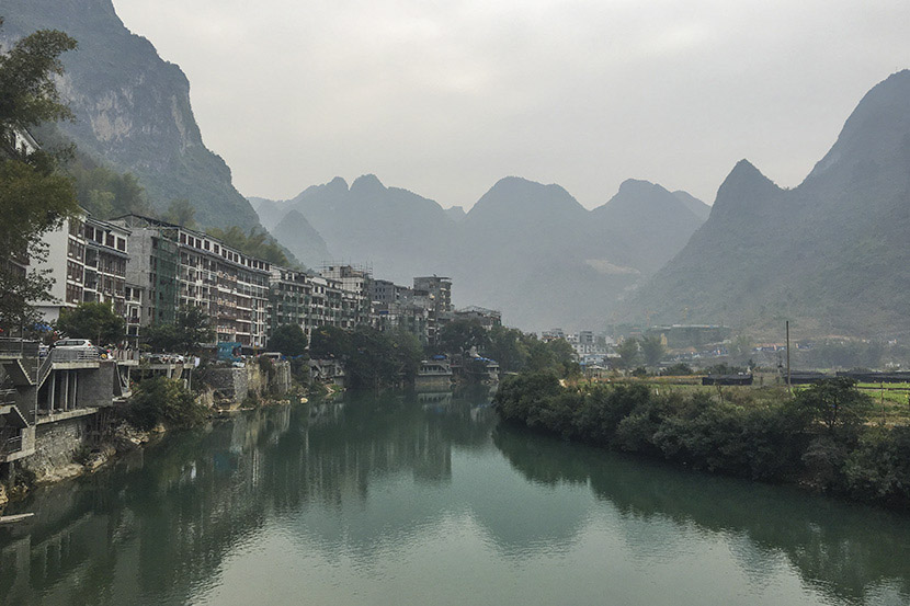 A view of Bapan Village and Panyang River in Bama County, Guangxi Zhuang Autonomous Region, Feb. 1, 2017. A number of high-rises have been built since 2009 to host the growing number of tourists. Fan Yiying/Sixth Tone