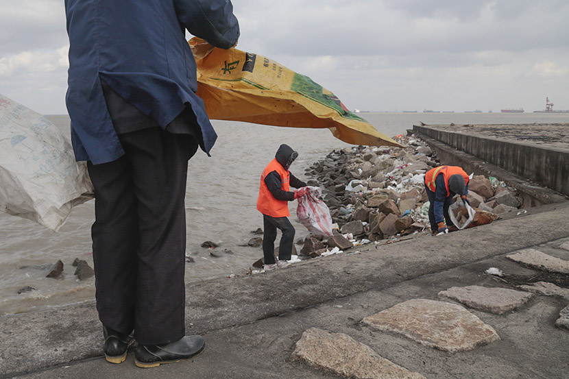 Sanitation workers pick up garbage along the banks of the Yangtze River, Taicang, Jiangsu province, Dec. 27, 2016. Li You/Sixth Tone