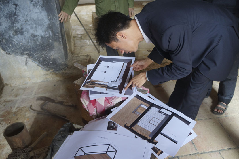 Lin Lusheng looks carefully at the construction plans for a 'shuyuan' at the Taoshu Building in Neilong Village, Yunxiao County, Fujian province, Feb. 8, 2017. Fan Yiying/Sixth Tone