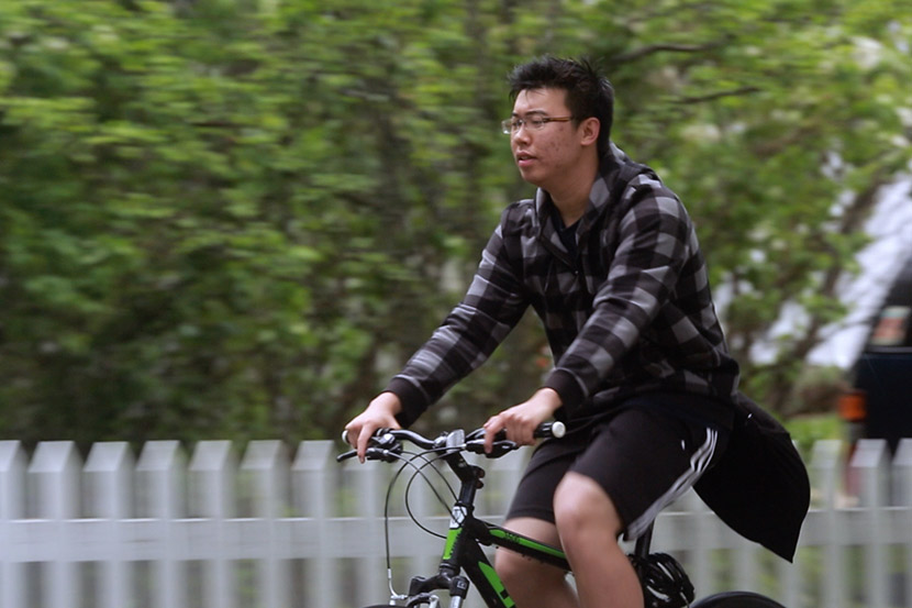 Harry rides a bike in a still from the documentary 'Maineland.' Courtesy of Wang Miao