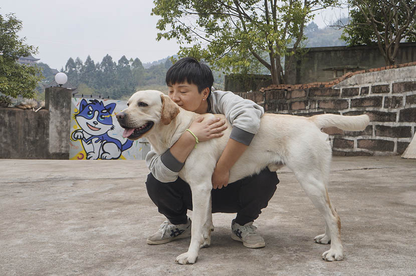 Fang Ling hugs Jian Jian at her dog hotel in rural Chengdu, Sichuan province, March 4, 2017. Fan Yiying/Sixth Tone