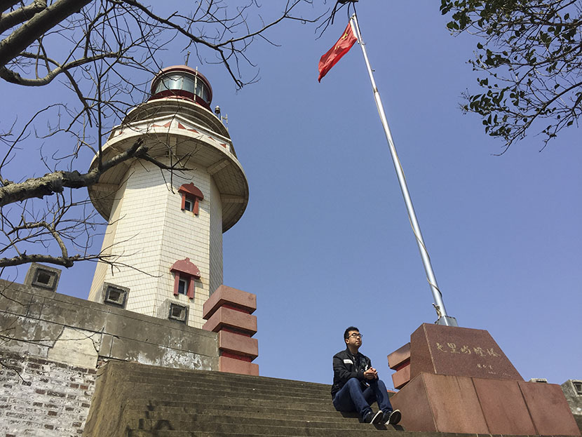 Ye Chaoqun sits outside the Qili Peak lighthouse after arriving to work a day early to avoid the strong winds predicted in the area, Zhejiang province, Feb. 28, 2017. Fu Danni/Sixth Tone