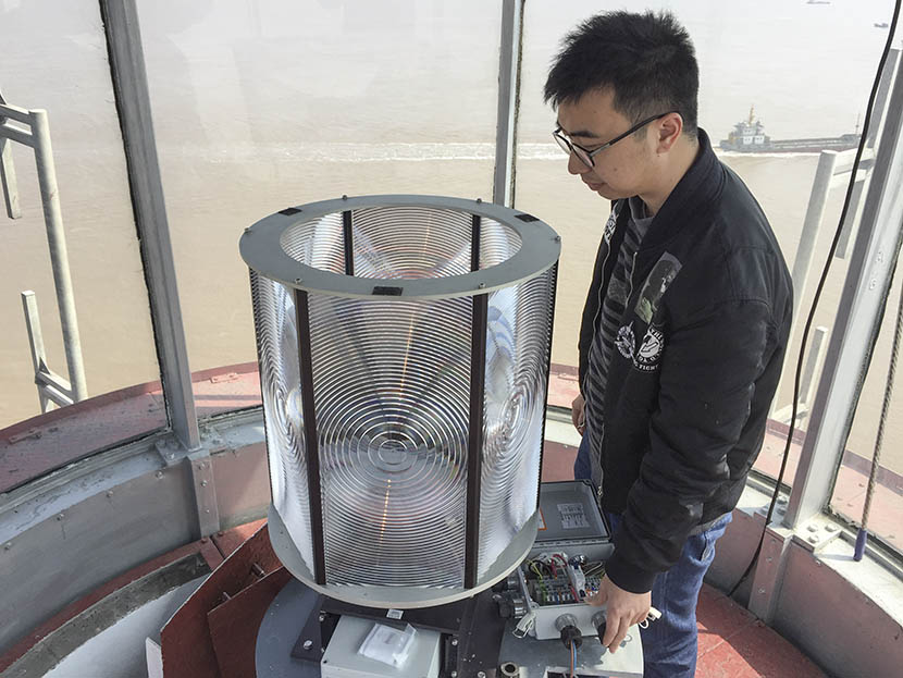 Ye Chaoqun demonstrates how to operate the light in Qili Peak's lighthouse, Zhejiang province, Feb. 28, 2017. Fu Danni/Sixth Tone