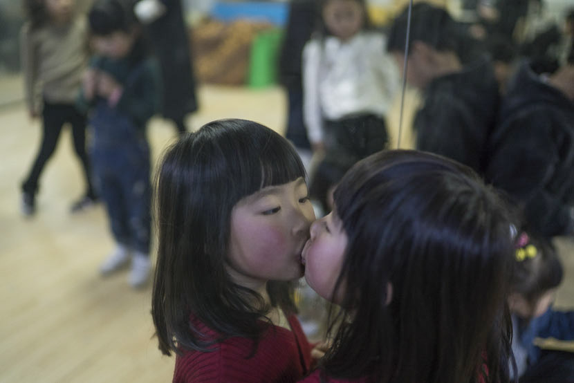 A girl kisses the mirror during the break of a child modeling class in Hangzhou, Zhejiang province, March 12, 2017. Wu Yue/Sixth Tone