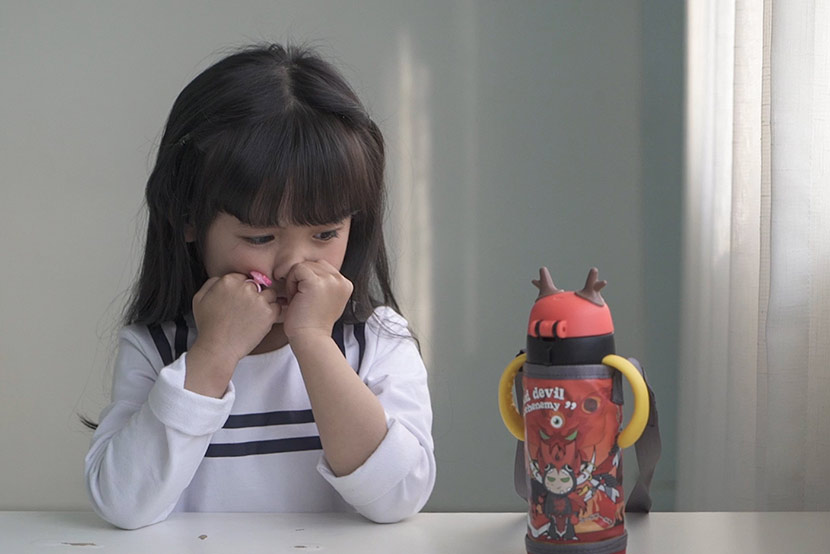 Five-year-old child model Huai Miluo stares at a water bottle — her prop — during a photo shoot in Hangzhou, Zhejiang province, March 2, 2017. Wu Yue/Sixth Tone