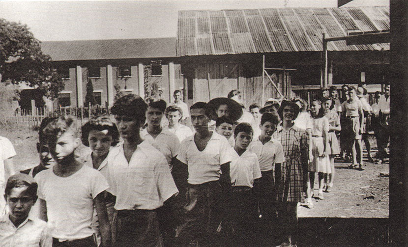 Lunghwa Academy students stand in line, with the camp's G Block residences visible in the background. Courtesy of Betty Barr