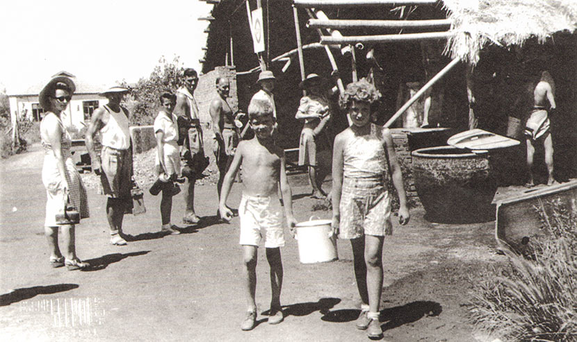 Children carry water from a hot water station in Lunghwa internment camp. Courtesy of Betty Barr