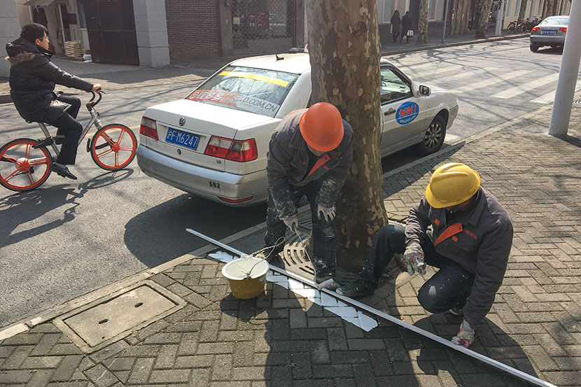 Workers paint a line designating a bicycle parking zone in Shanghai, Feb. 24, 2017. Kevin Schoenmakers/Sixth Tone