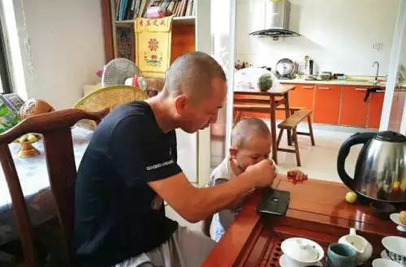 Dao Lu feeds a child at Husheng Xiaoju in Nantong, Jiangsu province. From WeChat public account Umalotus