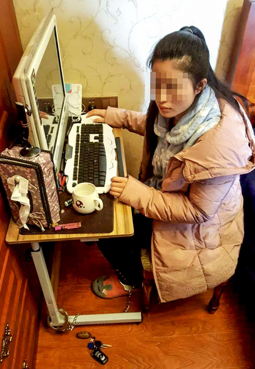 In a photo taken by a journalist accompanying local police, Ren Xin is seen shackled to a desk at the apartment she shares with her abusive husband in Chongqing, March 27, 2017. Chongqing Evening News/VCG