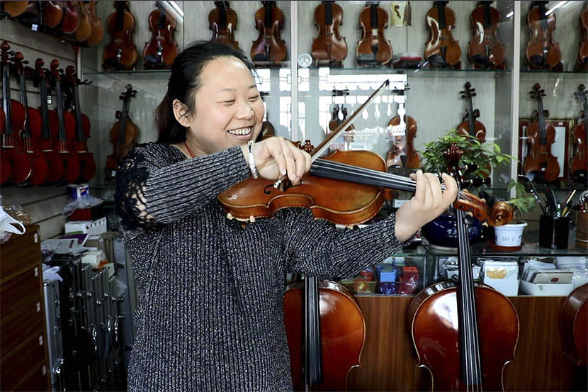 Ma Wei plays the violin in the shop where the band rehearse in Beijing, March 10, 2017. Yin Yijun/Sixth Tone
