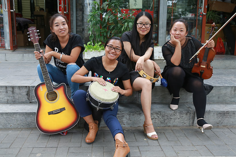 Duan Yu, Ren Juan, Xiong Ying, and Ma Wei pose for a photo in front of the violin shop where they rehearse in Beijing, Sept. 17, 2016. Courtesy of Jiu Ye