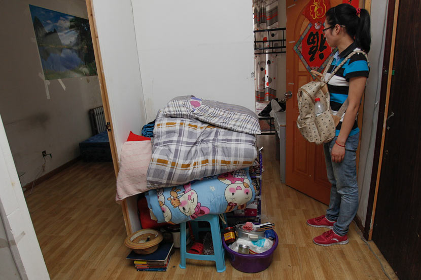 A tenant stands with her belongings after her 'secondary landlord' forced her to leave her apartment in Beijing, June 27, 2013. VCG