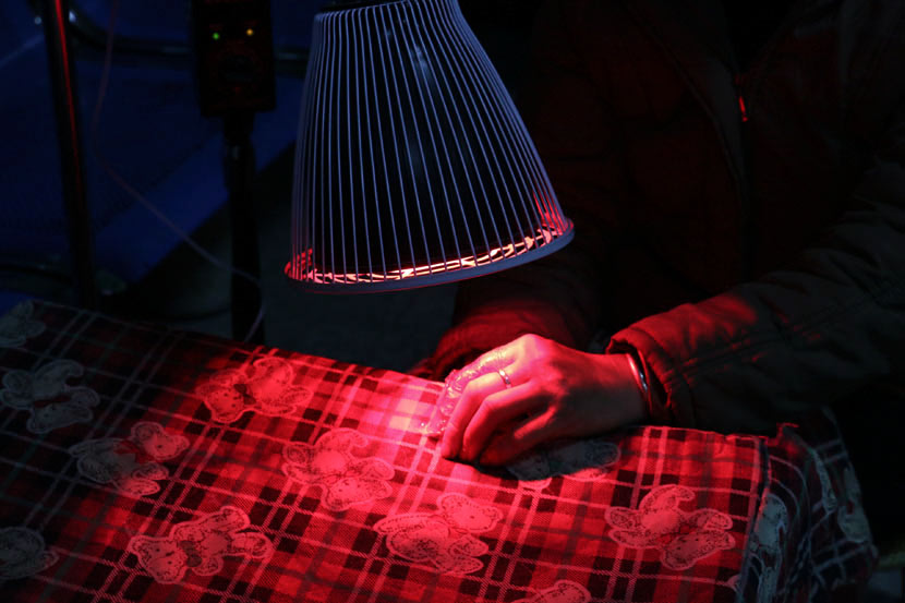 A village doctor uses infrared light to treat injuries and sore muscles in Gongcheng County, Guangxi Zhuang Autonomous Region, March 7, 2017. Cai Yiwen/Sixth Tone