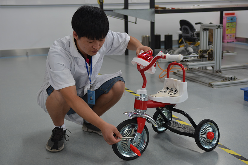 An employee at the Zhejiang Academy of Science and Technology for Inspection and Quarantine tests a toy following customer allegations that Niangao Mama had sold fake baby products, Hangzhou, Zhejiang province, 2016. Courtesy of Li Danyang