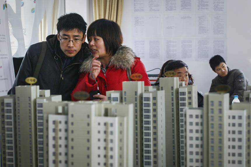 Homebuyers look at housing models at the sales center of a residential property project in Binhai New City, 19 Dec. 2006. Jia Lei/VCG